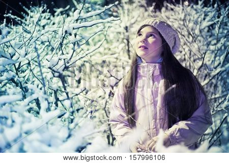 pretty preteen girl in knitted white hat and jacket on the snow bushes background under street light night scean