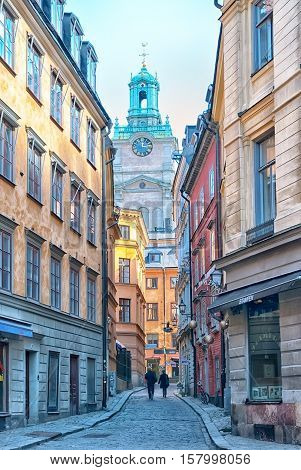 STOCKHOLM, SWEDEN - APRIL 14, 2010: People walk on Stora Gramunkegrand Alley in Gamla Stan. On the background is The Saint Nicolas Church. The alley is named after the defensive Greyfriar Tower