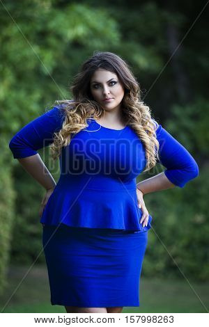 Young beautiful plus size model in blue dress outdoors with arms akimbo xxl woman on nature professional makeup and hairstyle
