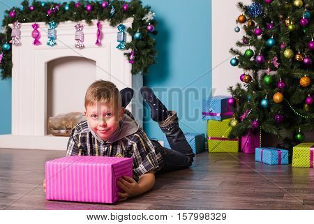 Smiling boyl lying on the floor next to the presents and a tree