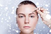 Young woman with short hair plucking eyebrows with tweezers close up woman plucking eyebrows depilating with tweezers. beauty people winter and health concept . over snow on gray background poster