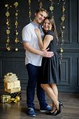Young man and the woman stand gently having embraced. They happily smile. Couple celebrates something. The dark wall is decorated with the shining garlands. On a floor beautifully packed gifts lie. poster