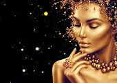 Gold Woman skin. Beauty fashion model girl with Golden make up, hair and jewellery on black background. Gold earrings, ring and necklace. Metallic, glance Fashion art portrait, Hairstyle and make up poster