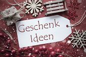 German Text Geschenk Ideen Means Gift Ideas. Nostalgic Christmas Decoration Like Gift Or Present, Sleigh. Card For Seasons Greetings With Red Paper Background. poster