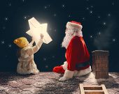 Merry Christmas and happy holidays! Cute little child girl and Santa Claus sitting on the roof and looking at Christmas star. Christmas legend concept. poster