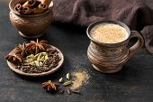 Masala pulled tea chai latte hot Indian sweet milk spiced drink, cinnamon stick, cloves, fresh spices and herbs blend, organic infusion healthy wellness beverage teatime ceremony in rustic clay cup poster