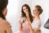 Bridesmaids and bride having fun. Delighted smiling young bride and bridesmaid sitting in the white room while drinking champagne and posing to the camera poster