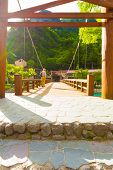 Tourist standing early morning on opposite bank of centered wooden Kappa Bashi Bridge with dramatic lens flare in the Japanese Alps village of Kamikochi Nagano Prefecture Japan. Vertical poster
