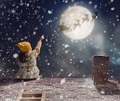 Merry Christmas and happy holidays! Cute little child girl sitting on the roof and looking at Santa Claus flying in his sleigh against moon sky. Kid enjoy the holiday. Christmas legend concept. poster