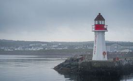 Red & white lighthouse in quiet Grand Bank, Newfoundland.  Gray, overcast morning on Atlantic shoreline.  A lone lighthouse atop an outcropping of rock at the end of a pier.