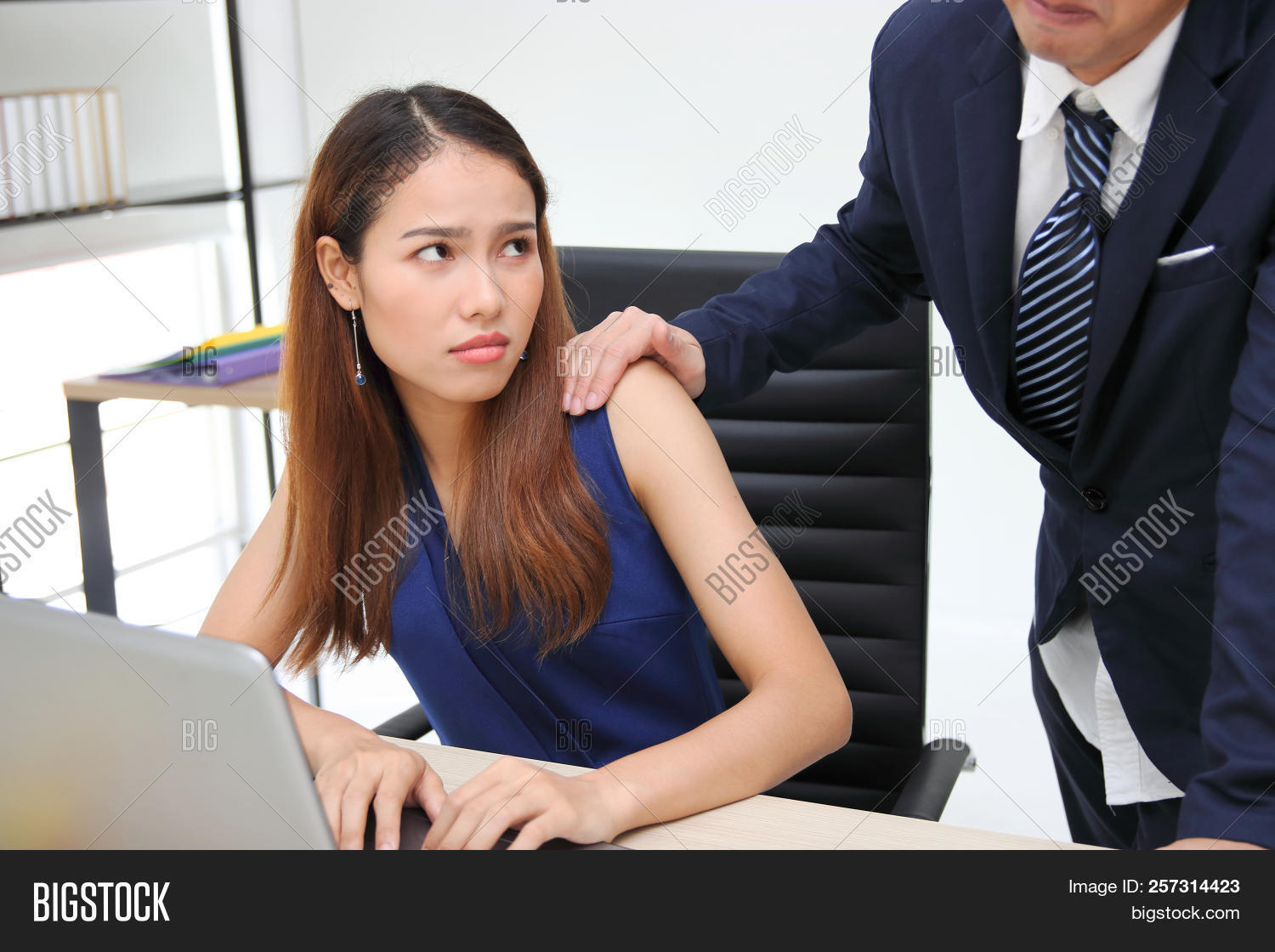 Angry Unhappy Asian Secretary Woman Looking Hand's Boss Touching Her  Shoulder In Workplace.