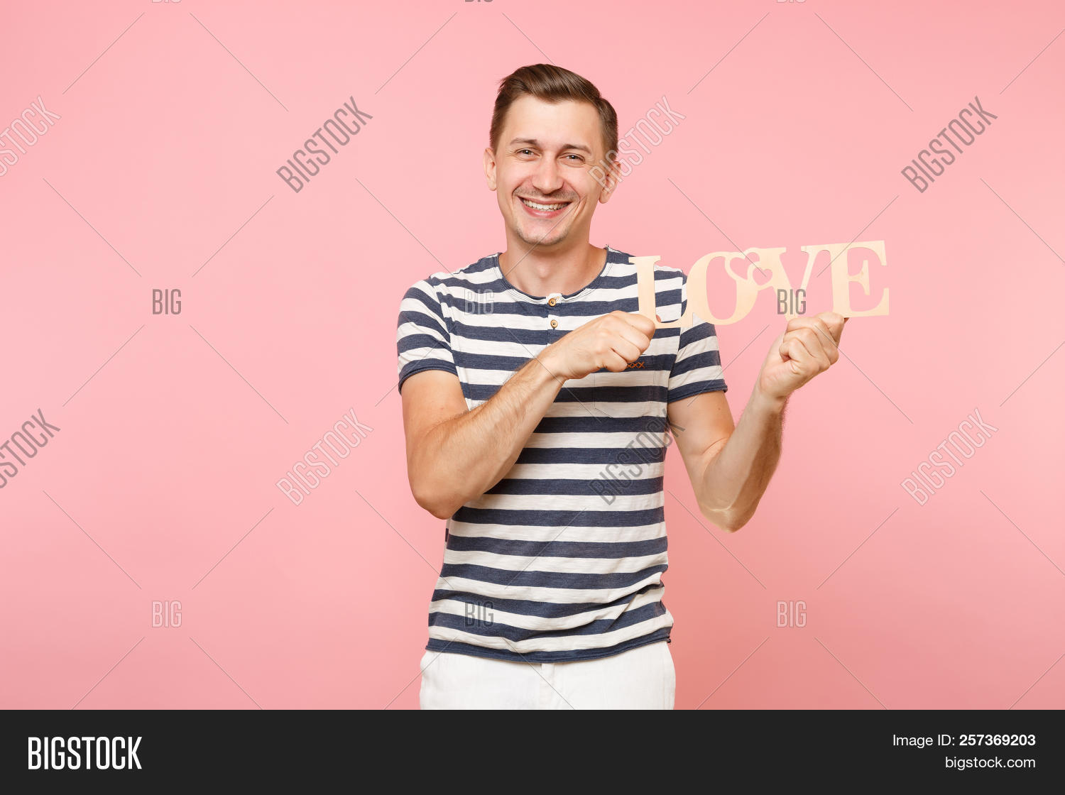 823bfca0 Portrait of smiling young man in striped t-shirt hold wooden word Love like  gun shoot isolated on trending pastel pink background.