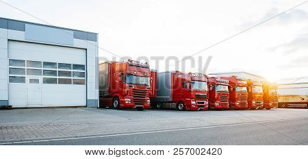 View Of Squadron Group Of New Red Cargo Trucks Parked In A Row Near Warehouse Building In Bright Sun