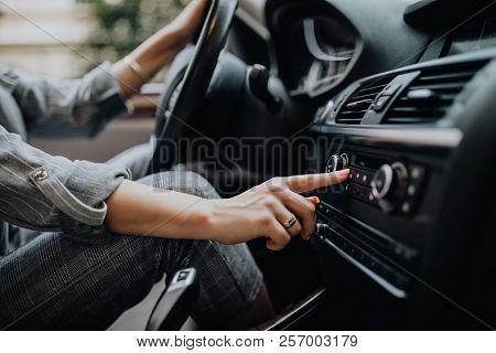 Car Dashboard. Radio Closeup. Woman Sets Up Radio While Driving Car