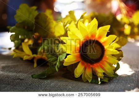 Garland made of faux sunfloewrs rest on a fabric cloth at an outdoor event