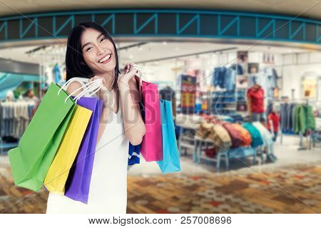 Beautiful Asian Woman With Shopping Bags In Clothes Shop. Sale, Shopping, Tourism And Happy People C