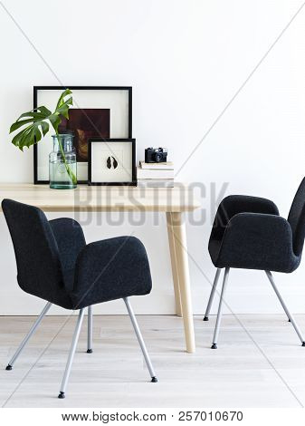Minimal Scandinavian Living Room With Black Chairs, Wooden Table And Elegant Posters