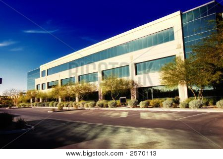 Modern commercial office exterior with late evening sun shining on windows poster