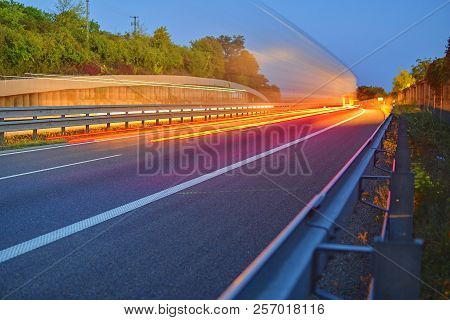 Highway At Twilight With Light Trails. High Traffic Road With Automobile Light Trails.