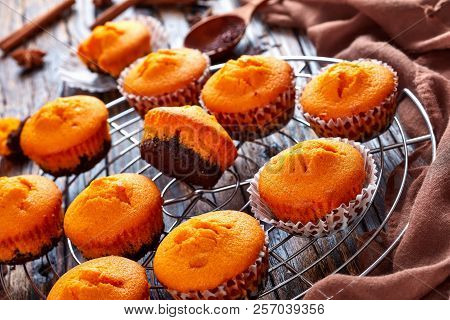 Close-up Of Freshly Baked Homemade Sweet Pumpkin Muffins  On A Round Stainless Steel Cake Cooling Ra