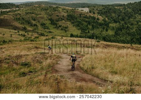 Back Two Cyclist On Mountainbikes Down Of Hill Along Trail