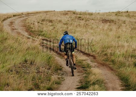 Back Male Cyclist Climbing Uphill On Mountain Bike Trail