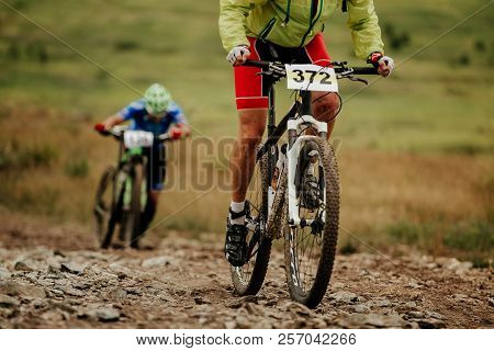 Two Athletes Cyclist Mountain Biking Uphill In Competition Xcm