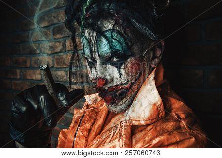 Halloween. Portrait of a bloodthirsty clown man over dark brick wall. Male zombie clown. Horror, thriller film. poster