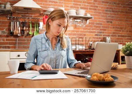 Young Woman In Savings And Home Budget Concept. Managing Finances, Taxes Using Calculator And Laptop