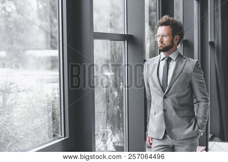 Young Pensive Businessman In Suit Looking Out Window In Office