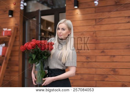 Young woman with bouquet of roses standing near store. Small business owner