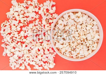 Paper Cup With Popcorn, And Popcorn Scattered On A Red Background, Top View, Copyspace. Flat Lay. Co