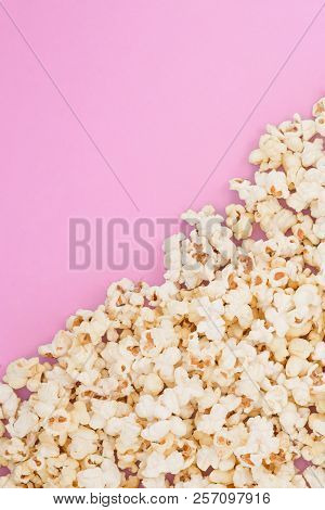 Popcorn Scattered At Half The Pastel Pink Background And A Space For Copyspace. Popcorn On A Red Bac