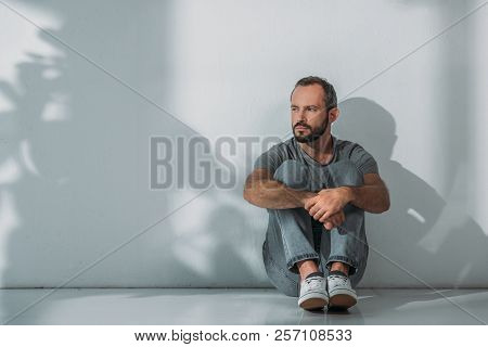Full Length View Of Depressed Bearded Middle Aged Man Sitting On Floor And Looking Away