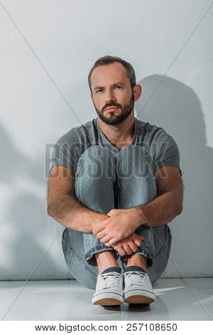 Full Length View Of Depressed Bearded Middle Aged Man Sitting On Floor And Looking At Camera