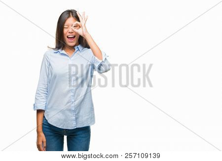 Young asian business woman over isolated background doing ok gesture with hand smiling, eye looking through fingers with happy face.