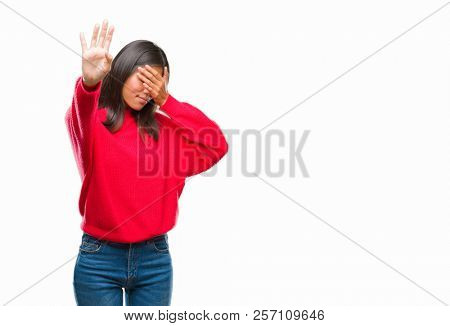 Young asian woman wearing winter sweater over isolated background covering eyes with hands and doing stop gesture with sad and fear expression. Embarrassed and negative concept. poster