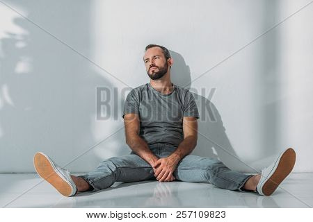 Full Length View Of Depressive Bearded Middle Aged Man Sitting On Floor And Looking Away