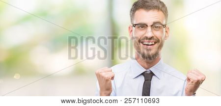 Young business man screaming proud and celebrating victory and success very excited, cheering emotion