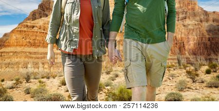 travel, hiking, backpacking, tourism and people concept - close up of couple with backpacks holding hands and walking along over grand canyon national park background