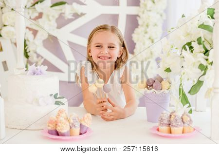 Little smiling blond girl holding colorful sweet lollipops on the background of pretty decorated candy bar poster