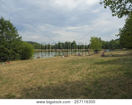Czech Republic, Marenice, August 3, 2018: People Rest On The Shore Of A Pond, Bathing And Swiming, S