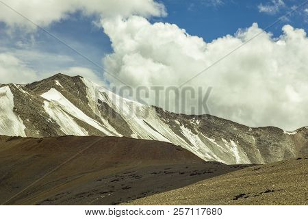 Desert Highlands With Snowy Mountains Peaks And Clouds