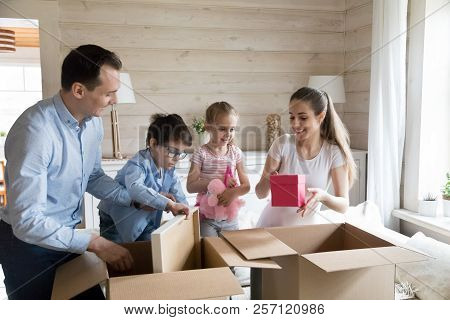 Happy Family Unpack Cardboard Boxes Moving To New Home
