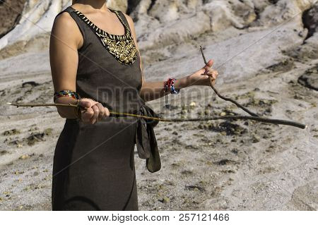 A Woman Searches For Water In A Desert Area By The Method Of Dowsing; Only Her Torso And Arms Are Vi