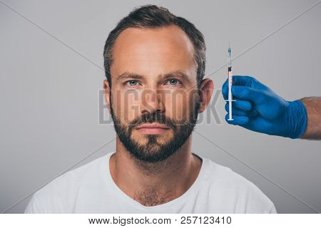 Doctor Holding Syringe In Hand And Man With Alopecia Looking At Camera Isolated On Grey