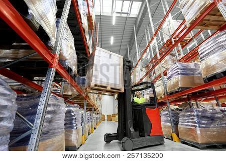 logistic business, shipment and loading concept - loader operating forklift with cargo at warehouse