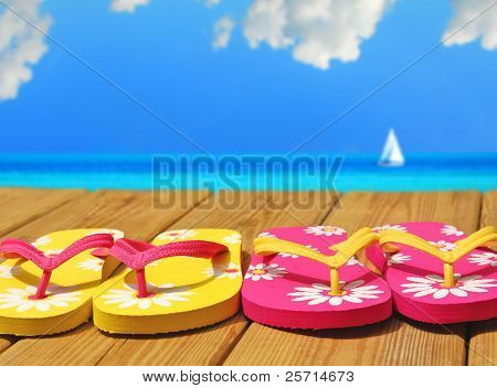 Colorful Flip Flops on Dock by Pretty Sea and Sailboat