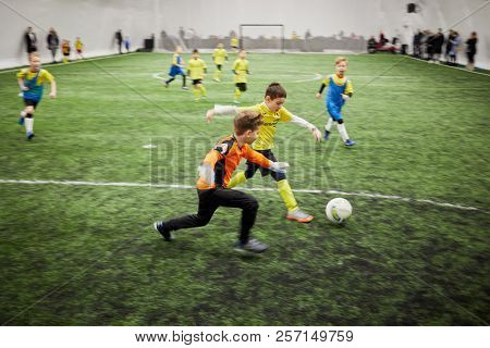 MOSCOW, RUSSIA - JAN 27, 2018: Forward and goalkeeper of children teams during children sport clubs cup soccer game at indoor sports ground of Krasnaya Presnya stadium.