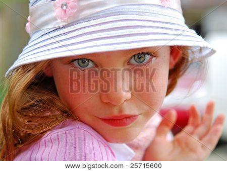 멋진 모자에 드레스를 재생 하는 어린 소녀